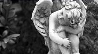 Fotografia rzeźby śpiącego aniołka.